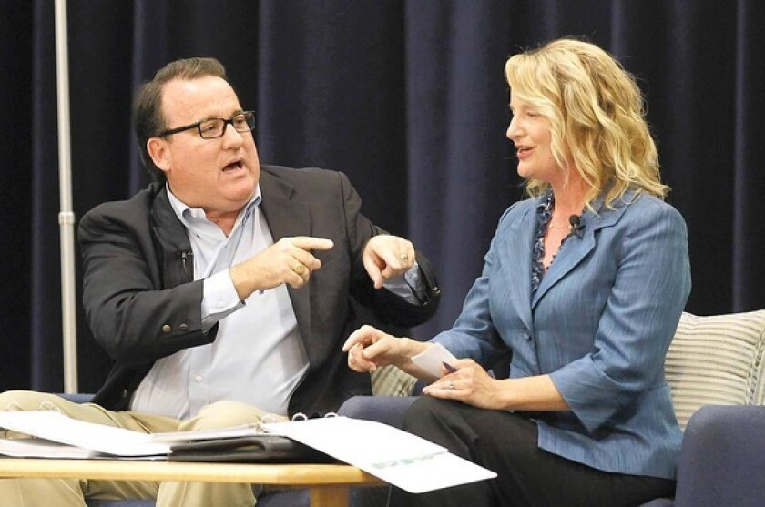 Costa Mesa Mayor Pro Tem Jim Righeimer, left, and Newport-Mesa Unified school board Trustee Katrina Foley have an animated discussion Monday night at the Neighborhood Community Center of the pros and cons of Costa Mesa having its own city charter.