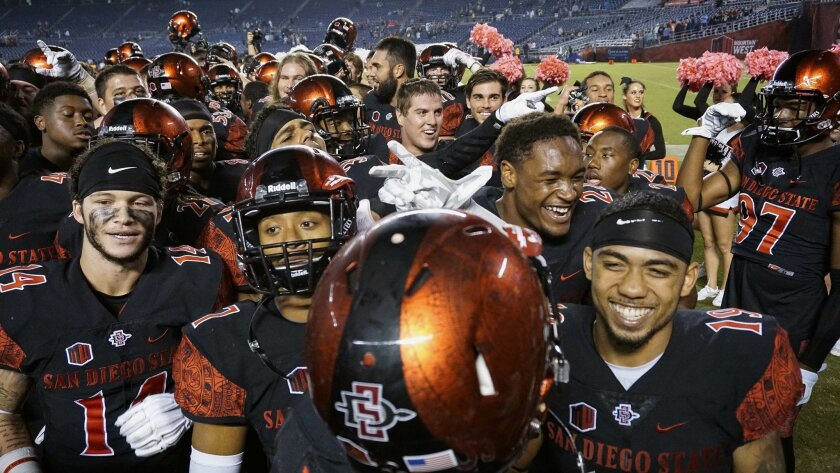 The Aztecs, including Donnel Pumphrey, lower right, celebrate the Aztecs 48-14 win over Utah State.