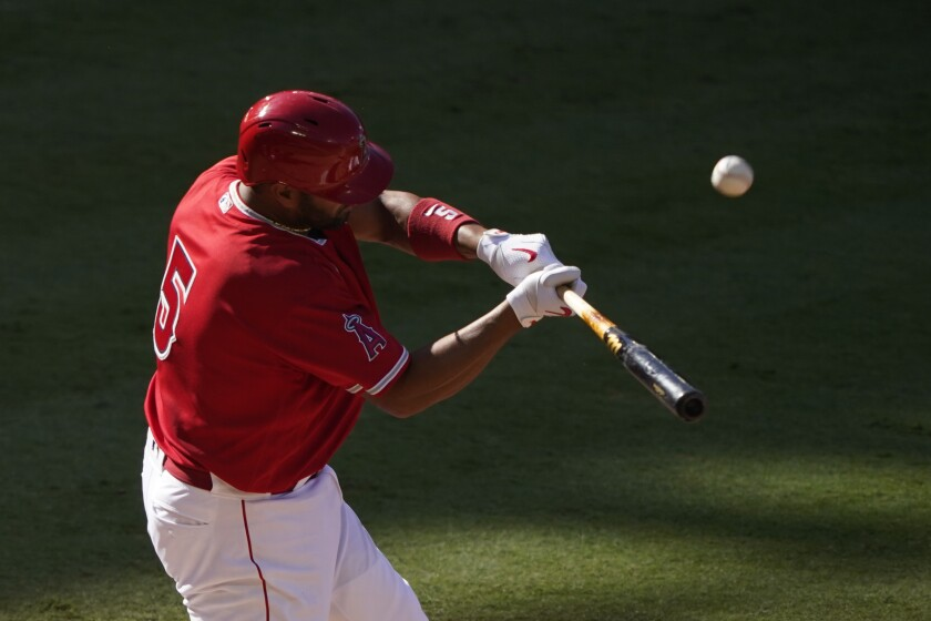 The ball pops off the bat as Albert Pujols takes a swing.