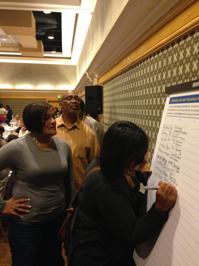 Participants line up to sign a declaration of principles at a weekend education conference in Los Angeles that took on corporate-inspired education reform.
