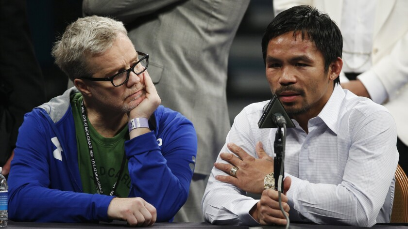 Manny Pacquiao speaks during a news conference Saturday while sitting next to his trainer, Freddie Roach, following his welterweight title loss to Floyd Mayweather Jr.