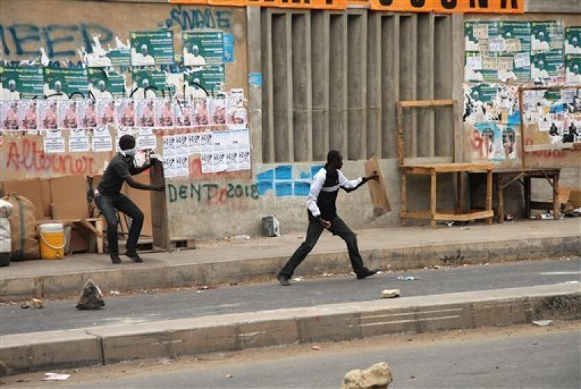 A young man throws a rock at riot police as another takes cover, during protests by students of Cheikh Anta Diop University in Dakar, Senegal Wednesday, Feb. 1, 2012. College students set fire to a bus and threatened to march on Senegal's presidential palace on Wednesday, a day after one of their c