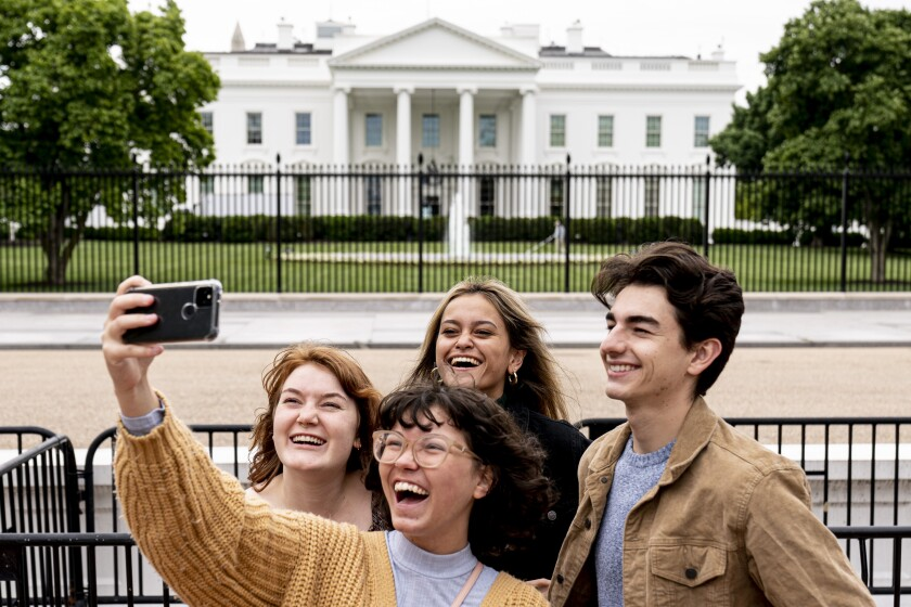 From left, Eliana Lord, Carly Mihovich, Stephanie Justice, and Nick Hansen, visiting from Columbia, S.C., take a photo at Lafayette Park, across the street from the White House, after it reopens in a limited capacity in Washington, Monday, May 10, 2021. Fencing remains in place around the park which will allow the Secret Service to temporarily close the park as they deem necessary. (AP Photo/Andrew Harnik)