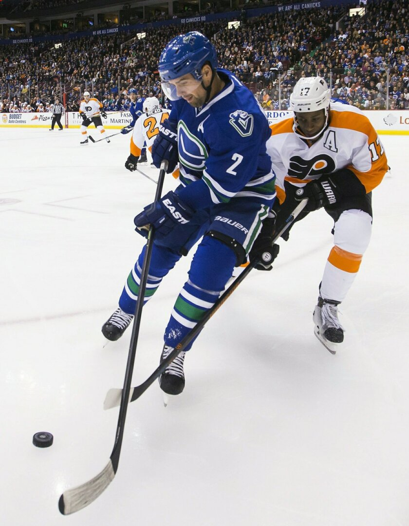 Vancouver Canucks' Dan Hamhuis (2) fights for the puck with Philadelphia Flyers' Wayne Simmonds (17) during the first period of an NHL hockey game in Vancouver, British Columbia, Monday, Nov. 2, 2015. (Ben Nelms/The Canadian Press via AP) MANDATORY CREDIT
