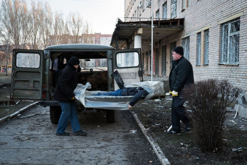 The body of a man killed by shelling that hit a hospital in Donetsk is removed on Wednesday.