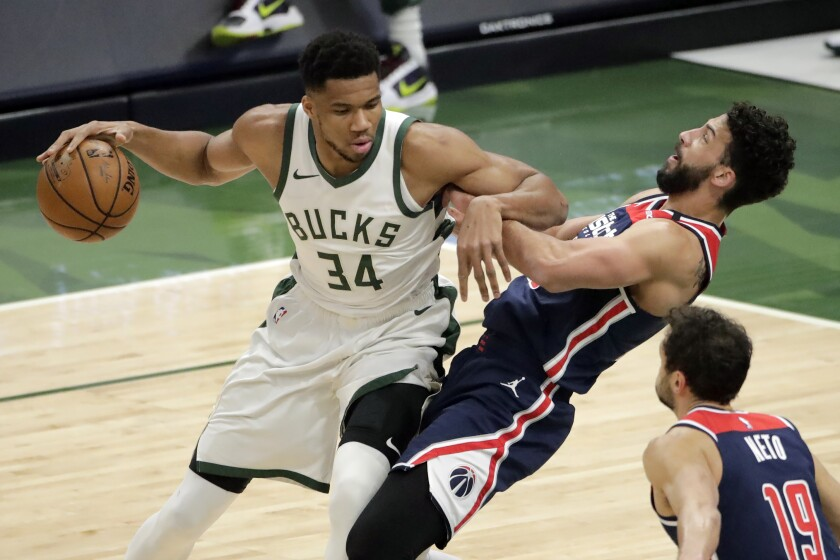 Milwaukee Bucks' Giannis Antetokounmpo (34) commits a charging foul against Washington Wizards' Anthony Gill during the first half of an NBA basketball game Wednesday, May 5, 2021, in Milwaukee. (AP Photo/Aaron Gash)