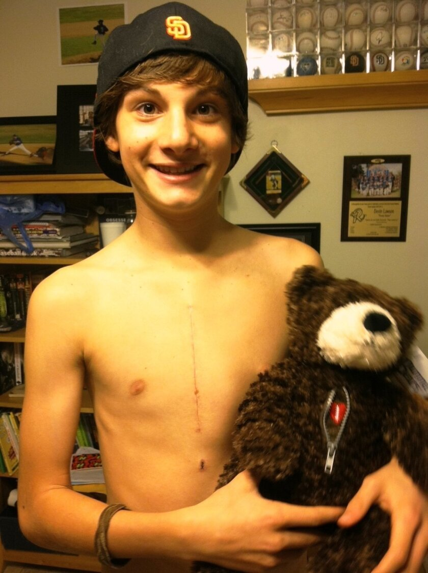 Devin Lawson, a Steele Canyon High senior, holds his heart teddy bear after open heart surgery three years ago. He was at risk for sudden cardiac arrest.