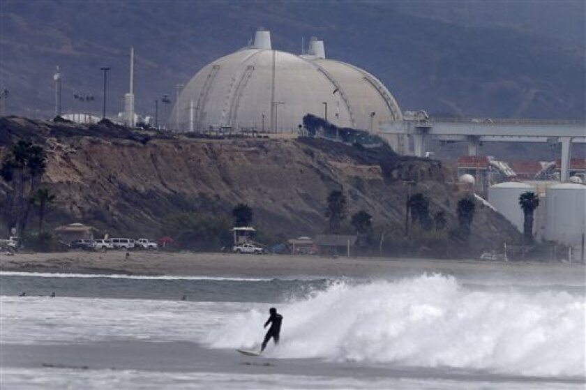 A surfer rides a wave in front of the San Onofre nuclear power plant Friday, June 7, 2013, in San Onofre, Calif. (AP Photo/Gregory Bull)