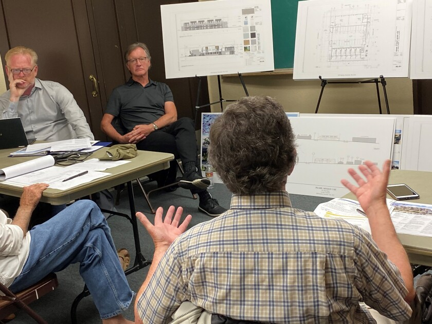 La Jolla Development Permit Review Committee chair Brian Will, left, listens as trustee Mike Costello, right, objects to the mixed-use residential and commercial project that owner David Bourne proposes for 801 Pearl St.