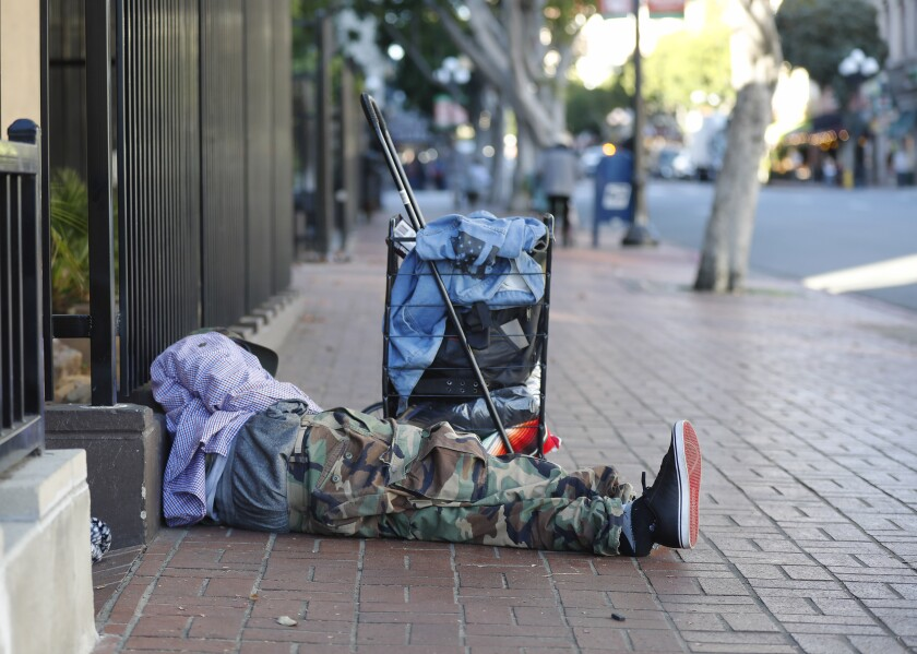 A homeless man sleeps on the sidewalk in downtown San Diego on Dec. 16, 2019.