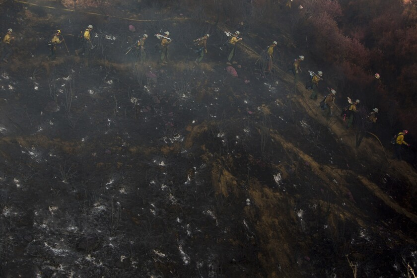 Hand crews line up to work on the remaining hot spots from a brush fire at the Apple Fire in Cherry Valley, Calif., Saturday, Aug. 1, 2020. (AP Photo/Ringo H.W. Chiu)