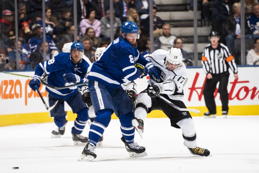 Toronto Maple Leafs defenseman Jake Muzzin, left, battles Kings forward Ilya Kovalchuk for the puck.