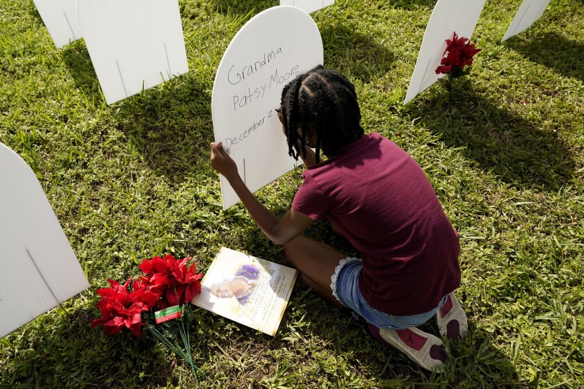FILE - In this Nov. 24, 2020, file photo, Kyla Harris, 10, writes a tribute to her grandmother Patsy Gilreath Moore, who died at age 79 of COVID-19, at a symbolic cemetery created to remember and honor lives lost to COVID-19 in the Liberty City neighborhood of Miami. As officials met to discuss approval of a COVID-19 vaccine on Thursday, Dec. 10, the number of coronavirus deaths has grown bleaker than ever. (AP Photo/Lynne Sladky, File)