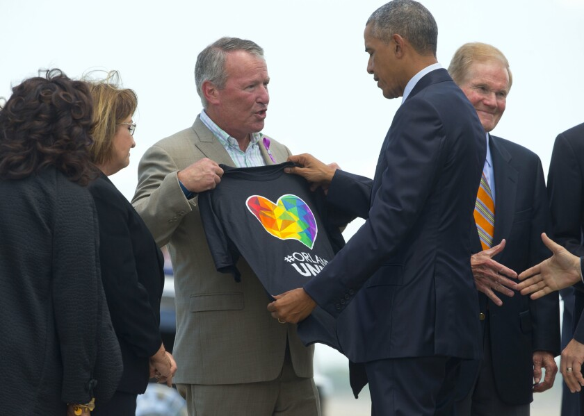 President Obama looks at a T-shirt that was presented to him by Orlando, Fla., Mayor Buddy Dyer, center, as Obama arrives in Orlando on Thursday.