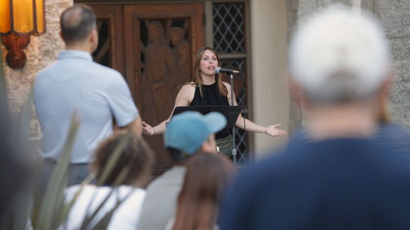 One of the event organizers, Erin Eisinger, speaks at the Lights for Liberty event at the La Cañada Congregational Church on Friday. The Nationwide Vigil to End Human Detention Camps.