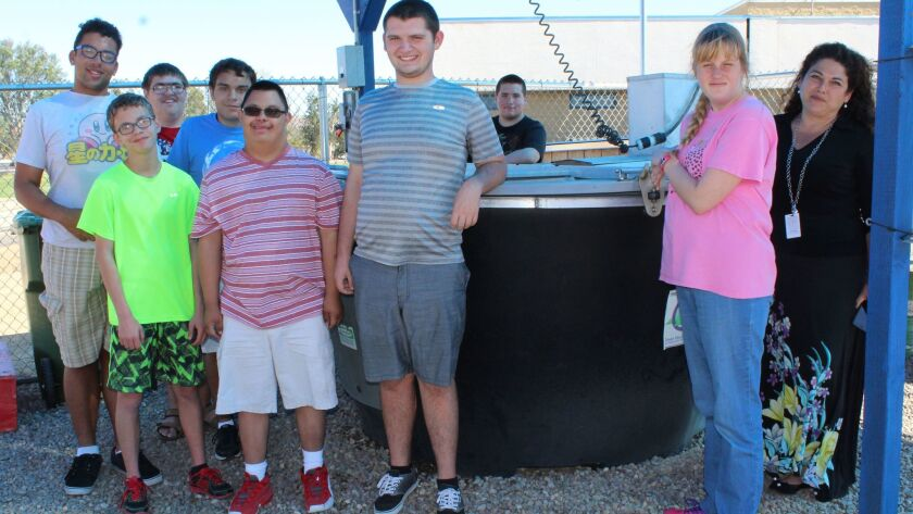 Standing with teacher Gloria Quinn by the Earth Tub composting system at Ramona High are students, from left, Reggie Moody, Shane DelReal, Chris Gilfoil, Alex Ramirez, Jonathan Villegas, Isaac Madsen, Nick Wiechert and Makayla Lucas.
