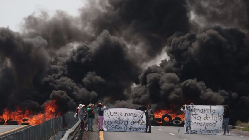 Villagers in Palmarito Tochapan, Mexico carry signs calling for peace and saying the town is in mourning on May 4, 2017, a day after clashes between soldiers and alleged fuel thieves.