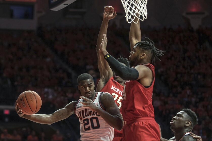 Illinois' DeMonte Williams (20) passes the ball under the basket around Maryland defender Donta Scott during the first half of an NCAA college basketball game Friday, Feb. 7, 2020, in Champaign, Ill. (AP Photo/Holly Hart)