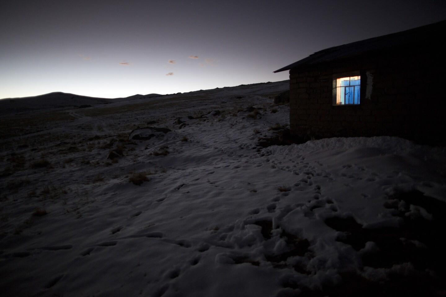 En esta fotografía la luz brilla a través de la ventana de una casa en medio de campos de nieve en San Antonio de Putina en la región de Puno, Perú, un área donde los locales crían alpacas y ovejas por su lana. Cada invierno el congelamiento destruye las praderas y hace difícil que los animales se alimenten. (AP Foto/Rodrigo Abd)