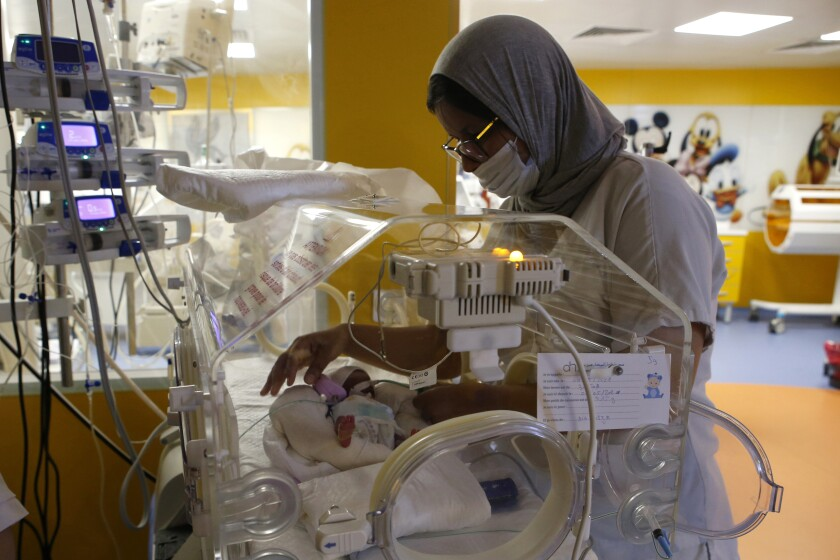 A Moroccan nurse takes care of one of the nine babies protected in an incubator at the maternity ward of the private clinic of Ain Borja in Casablanca, Morocco, Wednesday, May 5, 2021. A Malian woman gave birth to nine babies after n ' to have waited only seven, announced Wednesday the Ministry of Health of Mali. . Halima CissÈ, 25, gave birth by caesarean section Tuesday in Morocco after being sent there for special care, the ministry said. (AP Photo / Abdeljalil Bounhar)
