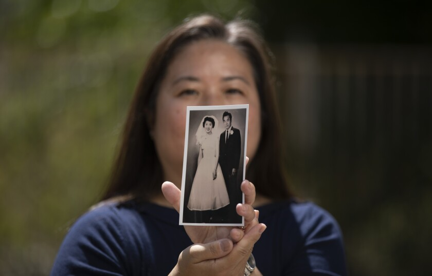 A woman holds up a back-and-white picture of a bride and groom.