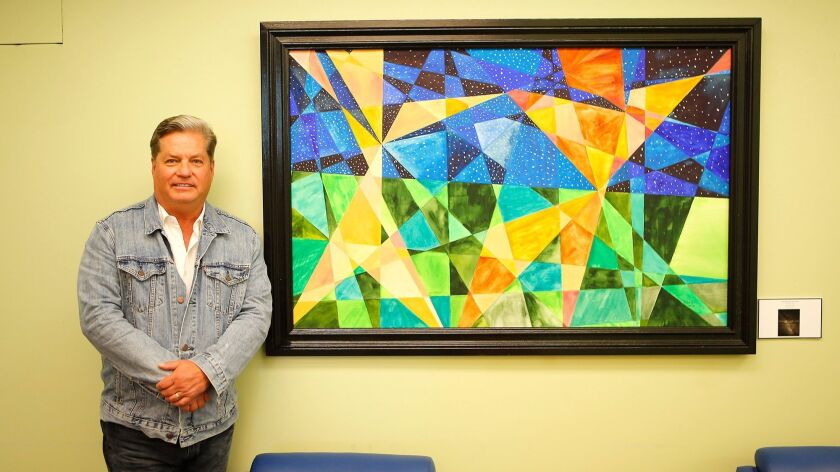 Chip Fesko stands next to one of his vertical abstract geometric paintings, based on math lines, on