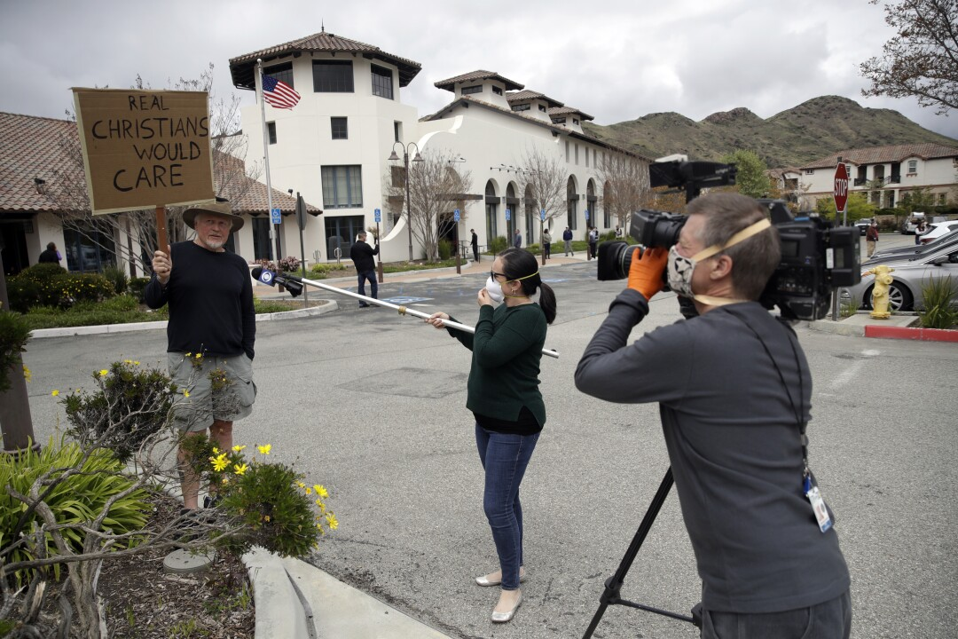 CALIFORNIA: Reporters practice social distancing as they interview Andrew Goetze, left, who protested a service at Godspeak Calvary Chapel on Sunday in Newbury Park, Calif.