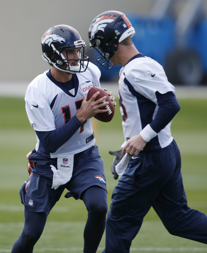 Denver Broncos backup quarterback Brock Osweiler, back, looks to pass under pressure from starting quarterback Peyton Manning during an NFL practice session at the team's headquarters Wednesday, Nov. 4, 2015, in Englewood, Colo. (AP Photo/David Zalubowski)