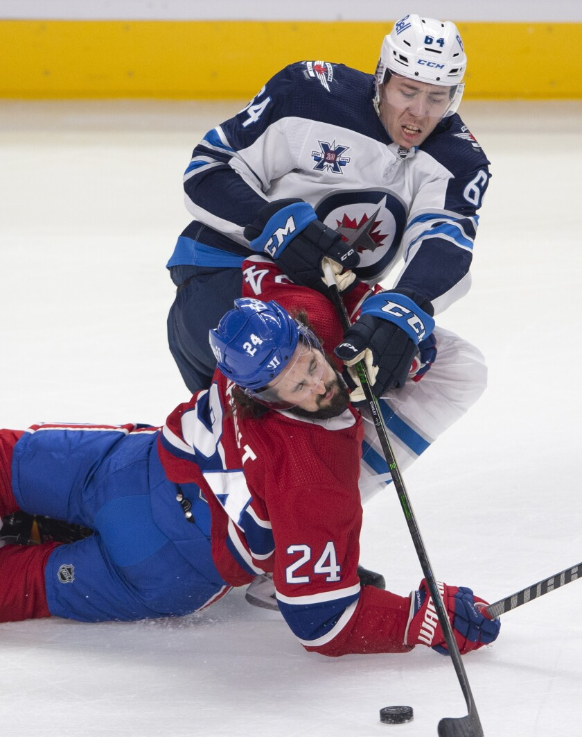 Montreal Canadiens' Phillip Danault (24) falls to the ice as he battles for a loose puck with Winnipeg Jets' Logan Stanley (64) during the first period of an NHL hockey game, Thursday, April 8, 2021 in Montreal. (Ryan Remiorz/The Canadian Press via AP)