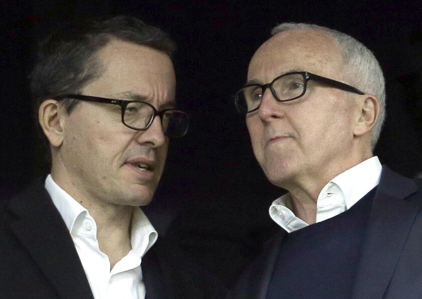 FILE - In this Sunday, Nov. 20, 2016 file photo, owner of the Olympique de Marseille soccer club, Frank McCourt, right, speaks to Olympique Marseille President Jacques-Henri Eyraud during the League One soccer match between Marseille and Caen, in Marseille, southern France. Marseille must pay UEFA several millions euros (dollars) for breaking rules that monitor club finances but retains its Champions League place. Their place in the Champions League group stage was earned by coach Andre Villas-Boas's team being second to French champion Paris Saint-Germain when the league was ended early during the pandemic. Villas-Boas revived the 1993 European champion after being hired by Frank McCourt, the former Los Angeles Dodgers owner. (AP Photo/Claude Paris, file)