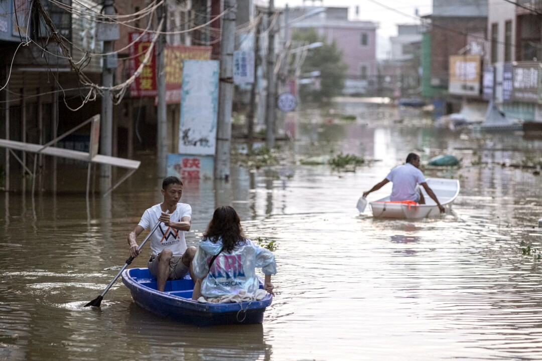 Villagers paddle boats through the flooded main street of Dixi village at dusk.
