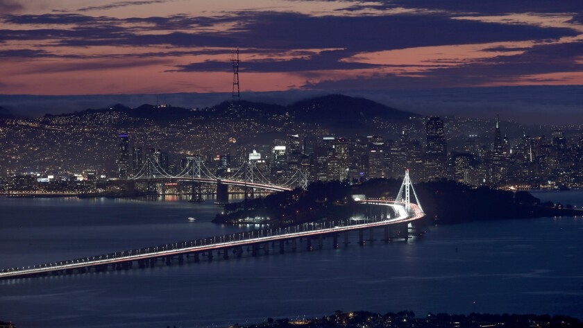 A colorful sunset over the San Francisco-Oakland Bay Bridge. The summer solstice inspires scientific study and ritual observations.