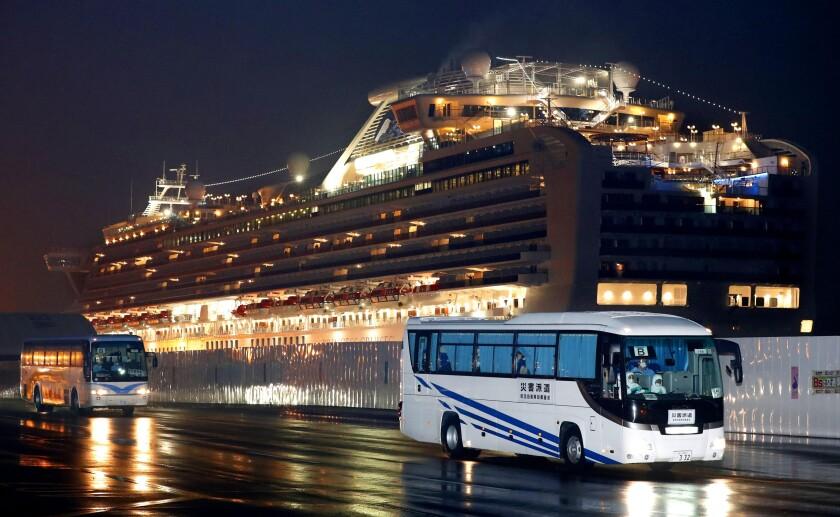 Buses carrying U.S. passengers who were aboard the quarantined cruise ship Diamond Princess, seen in the background, leave Yokohama, Japan, on Feb. 17. The cruise ship was carrying nearly 3,500 passengers and crew members under quarantine.