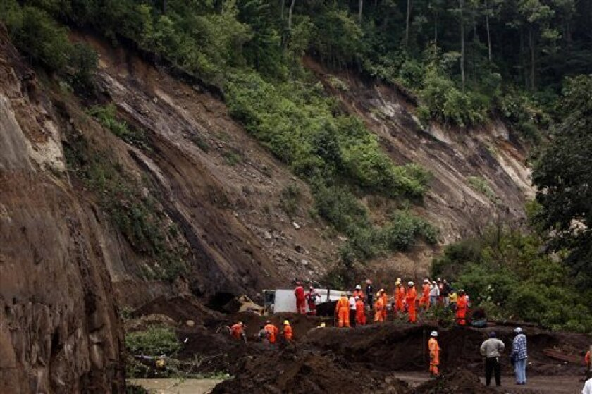 Rescue workers look for survivors at a mudslide area in Nahuala, western Guatemala, Sunday, Sept. 5, 2010. At least 38 people were killed after torrential rains caused mudslides in different areas of the country, injuring 20 others and leaving over 60 people missing. (AP Photo/Moises Castillo)