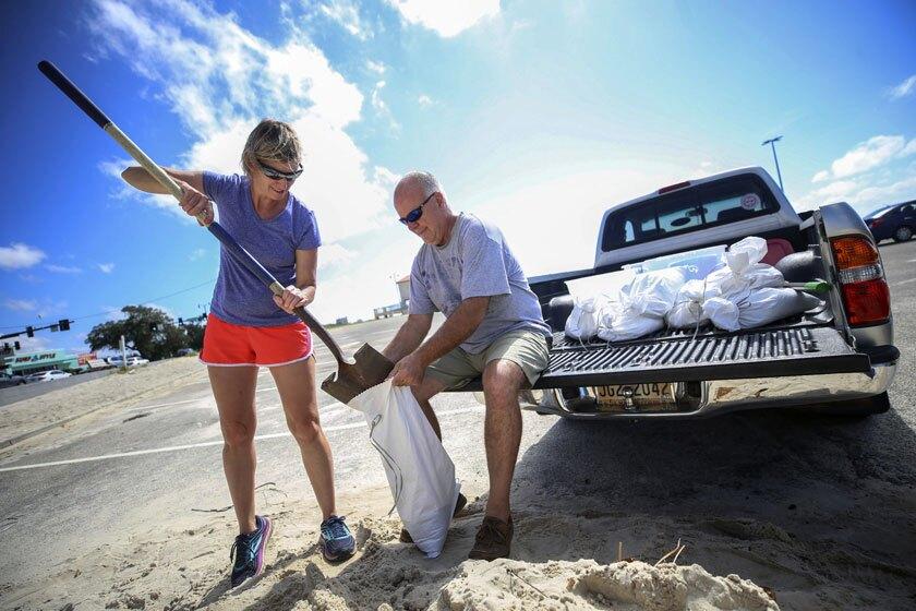 Two people fill sandbags