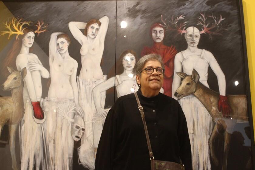 """Judithe Hernández frente a su obra """"Les demoiselles d'barrio"""", basada en una pintura de Picasso."""