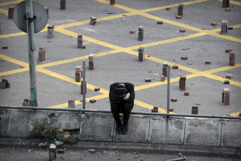A protester sits near stacks of bricks that were used to barricade a road Nov. 14 near Hong Kong Polytechnic University.