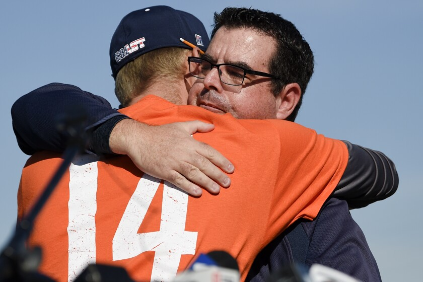 Associate coach Nate Johnson, left, hugs Tony Altobelli during a ceremony held for John Altobelli, the late head coach of Orange Coast College baseball, who died in a helicopter crash alongside former NBA basketball player Kobe Bryant in Costa Mesa, Calif., Tuesday, Jan. 28, 2020. His wife Keri and youngest daughter Alyssa were also victims of the crash. (AP Photo/Kelvin Kuo)