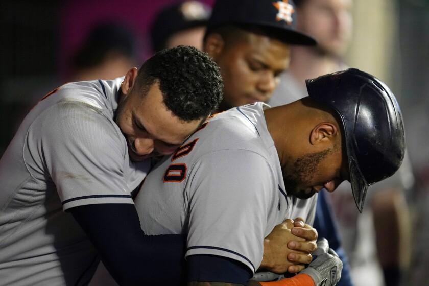 El jugador de los Astros de Houston Martín Maldonado (derecha) recibe el abrazo de su compañero Carlos Correa tras sacudir un jonrón solitario en el sexto inning del juego de la MLB que enfrentó a su equipo con los Angelinos de Los Ángeles, el 21 de septiembre de 2021, en Anaheim, California. (AP Foto/Marcio José Sánchez)