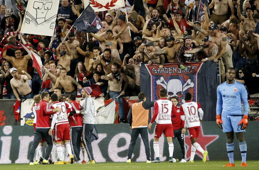 New York Red Bulls players, bottom left, celebrate a goal by forward Bradley Wright-Phillips (99) against D.C. United during the second half of an MLS playoff soccer match, Sunday, Nov. 8, 2015, in Harrison, N.J. The Red Bulls won 1-0. United goalie Bill Hamid, right, looks on. (AP Photo/Julio Cort
