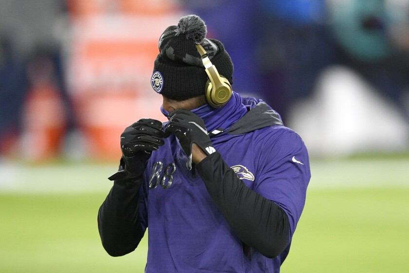 Baltimore Ravens wide receiver Dez Bryant adjusts his face covering while working out prior to an NFL football game against the Dallas Cowboys, Tuesday, Dec. 8, 2020, in Baltimore. (AP Photo/Nick Wass)