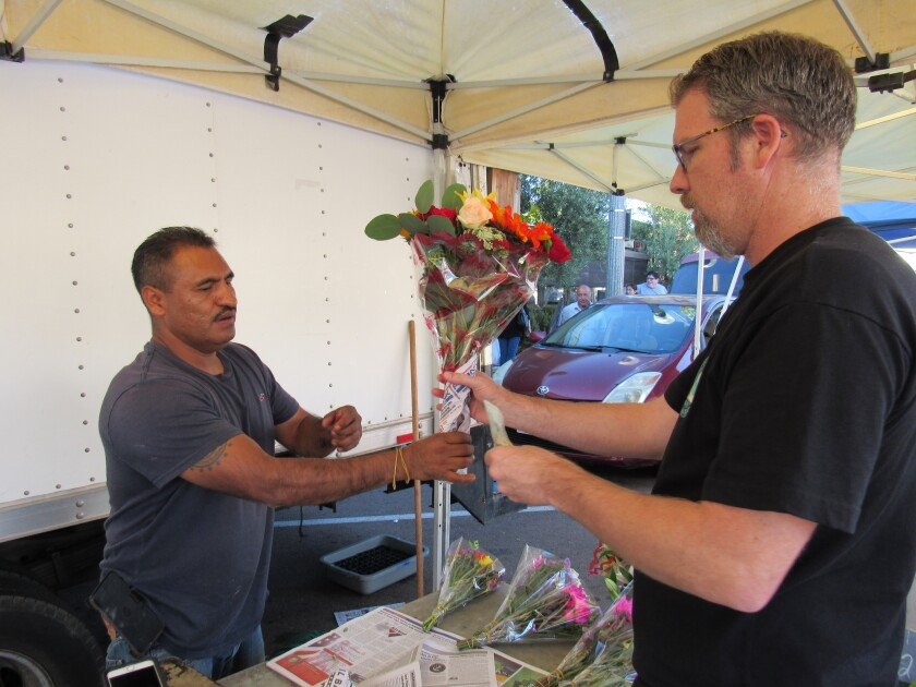 Fabian Ramos of Hidalgo Flowers hands a bouquet of fresh flowers to customer Kent Coston of La Mesa at a recent Friday farmers market in downtown La Mesa. The City Council last week agreed to keep the event on the same day at the same location in the village for one year.
