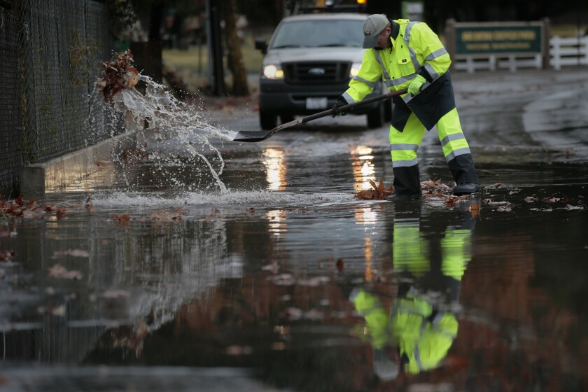 San Dimas Public Works Supervisor Terry Gregory clears a clogged drain in January as heavy rains caused flooding and mud flows in San Dimas, Glendora and Azusa.