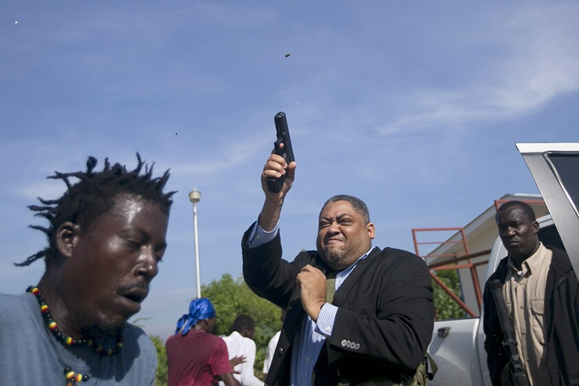 Sen. Ralph Fethiere fires his gun outside Haiti's Senate in Port-au-Prince on Monday. Fethiere, who is from the governing party, pulled a pistol when protesters rushed at him and members of his entourage.