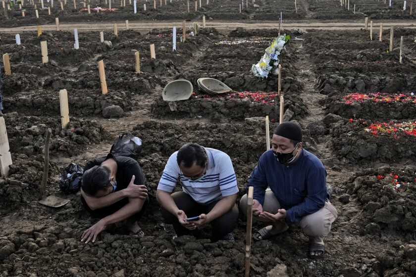 Men pray during the burial of a relative at Rorotan Cemetery which is reserved for those who died of COVID-19, in Jakarta, Indonesia, Thursday, July 1, 2021. New land around the capital city continues to be cleared for the dead and gravediggers have to work late shifts following surges in COVID-19 cases fueled by travel during the Eid holiday in May, and the spread of the delta variant of the coronavirus first found in India. (AP Photo/Dita Alangkara)