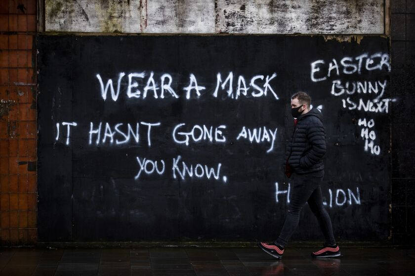 A man wearing a face covering walks past graffiti on the Lower Newtownards Road in Belfast with a message reading 'Wear a mask, it hasn't gone away you know' Friday, Jan. 1, 2021. (Liam McBurney/PA via AP)