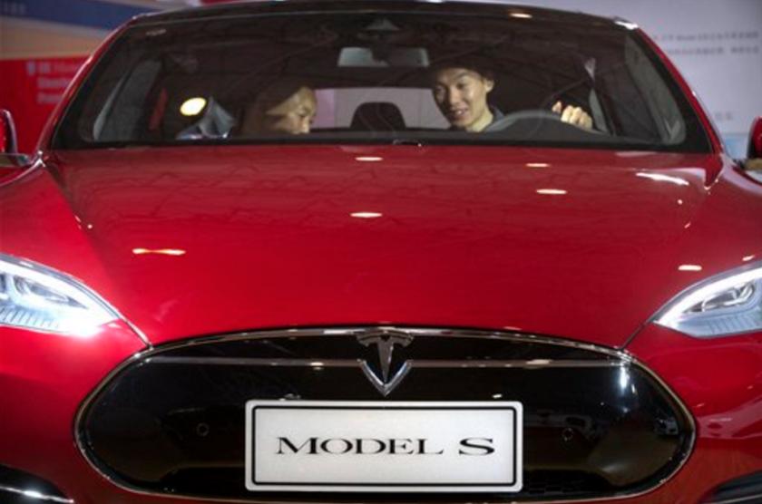 Esta foto muestra a un hombre detrás del volante de un auto eléctrico Tesla Model S que estaba siendo mostrado en la Exposición Internacional de Automoviles de Beijing, en Beijing. (Foto AP /Mark Schiefelbein, Archivo)