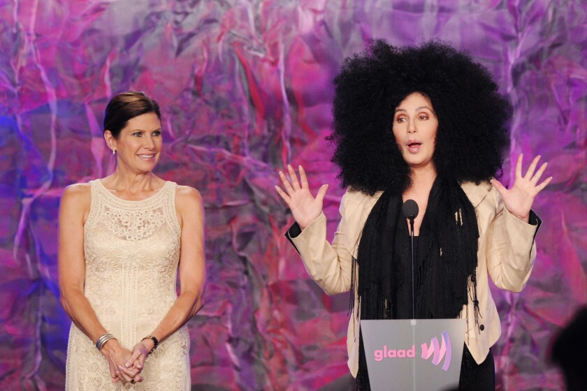Two women stand onstage to accept an award