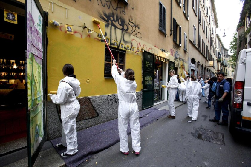 Demonstrators paint a wall covered by writings in Milan, Italy, Sunday, May 3, 2015 during a march to protest violence that left much of downtown trashed on May Day. Hundreds of the marchers removed graffiti and helped repair other damage wreaked by protesters who rampaged through downtown two days earlier while VIPs were inaugurating the world's fair the city is hosting, Expo 2015, opened on its outskirts. (Mourad Balti Touati/ANSA via AP)