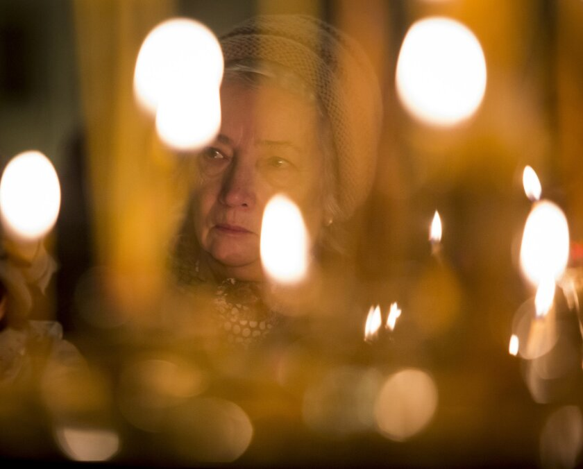 A woman takes part in a memorial religious service for plane crash victims at the St.Isaac's Cathedral in St.Petersburg, Russia, Sunday, Nov. 8, 2015.  Mourners have packed into the landmark St. Isaac's Cathedral in St. Petersburg for a memorial service for victims of the Russian plane crash, and a